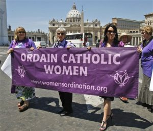 Representatives of the Women's Ordination Conference stage a protest in front of St.Peter's Basilica, in Rome, with from left, Therese Koturbash from Dauphin, Matitoba, Canada, Mary Ann Schoettly from Newton, N.J, US, and Erin Saiz Hanna, Washington, D.C. US, as they protest on Tuesday, June 8, 2010. Groups that have long demanded that women be ordained Roman Catholic priests took advantage of the Vatican's crisis over clerical sex abuse to press their cause demanding the Vatican open discussions on letting women join the priesthood. (AP Photo/Pier Paolo Cito)